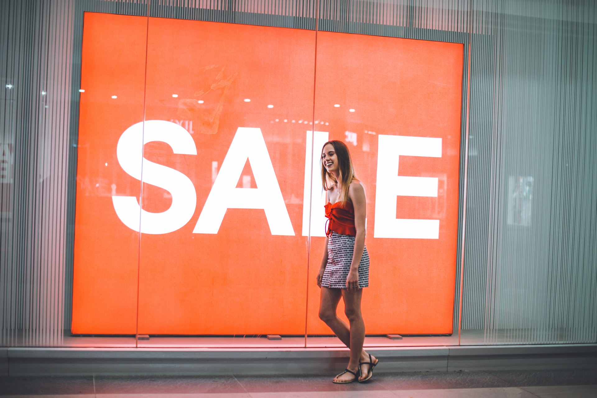 Woman-In-Front-Of-Orange-Sale-Sign