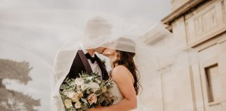 Bridge and groom kissing with bride holding bouquet