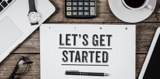 """Desk with a notebook that shows """"Let's Get Started"""""""