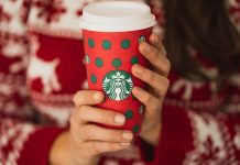 Woman with a red holiday sweater holding a holiday Starbucks cup with both hands