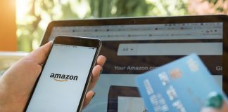 Woman holding phone with Amazon logo on left hand and a credit card on her right hand