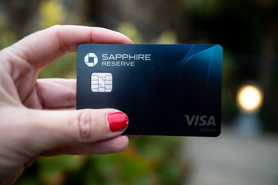 Woman with red nails holding a Chase Sapphire Reserve credit card
