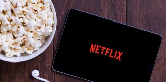 Netflix and popcorn on wooden table