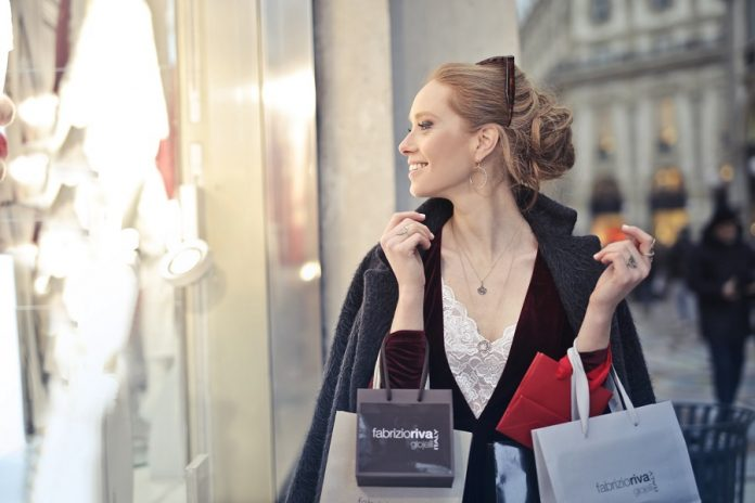 Woman smiling while window shopping and holding shopping bags