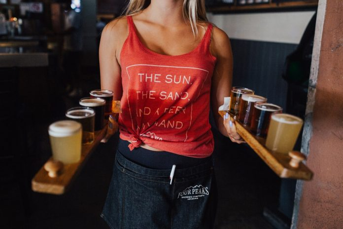 Waitress in tank top holding two beer trays