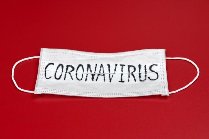 Coronavirus written on a mask over red background