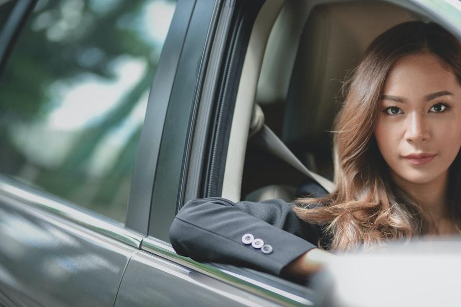 Woman in black blazer sitting inside car