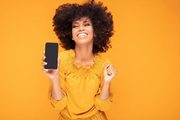 Young woman holding phone with orange background