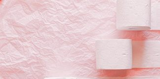 White toilet paper rolls on pink textile background