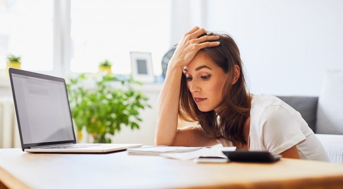 Young woman struggling looking at bills