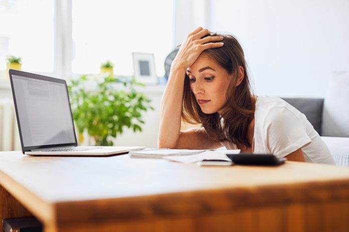 Young woman struggling looking at bills