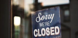 """Sorry we're closed"" sign on window"