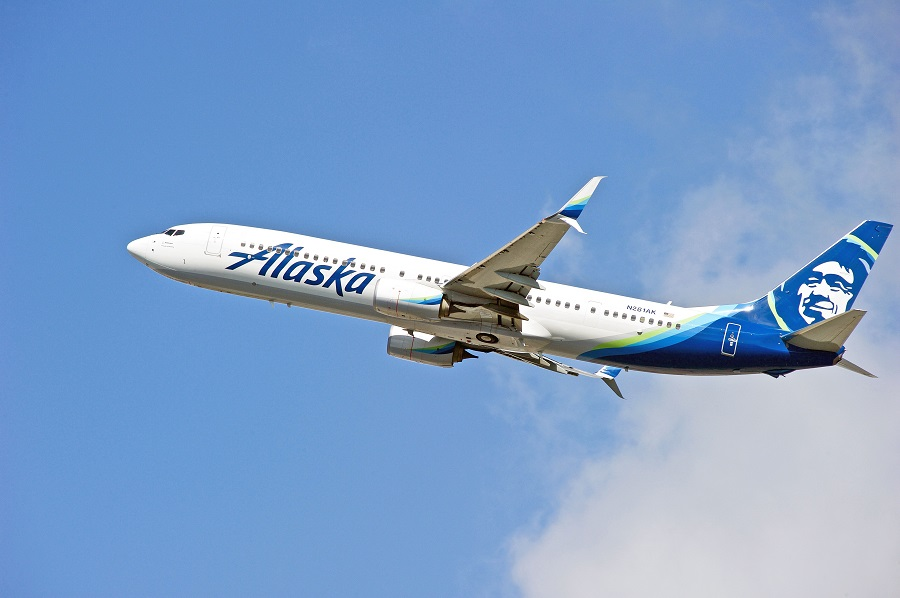 Alaska Airlines plan flying in sky with clouds