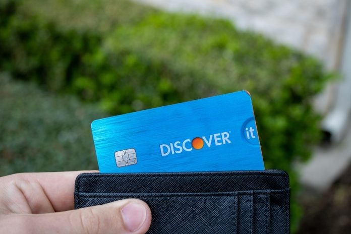 Man holding Discover It card inside wallet