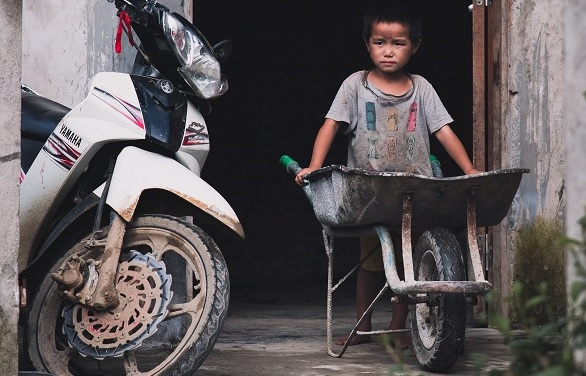 Poor boy holding a wheelbarrow in Vietnam
