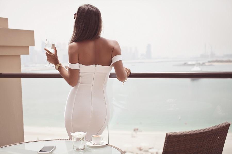 Wealthy woman on balcony overlooking ocean and skyscrapers