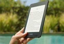 Black Kindle held by a woman's hand around water
