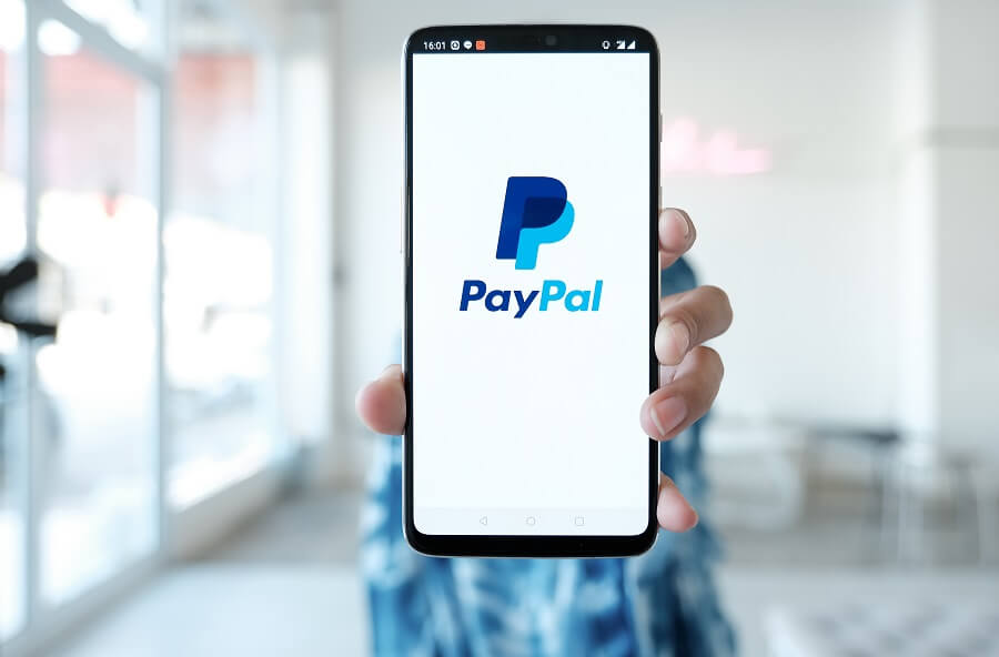 Person holding phone with PayPal logo on it